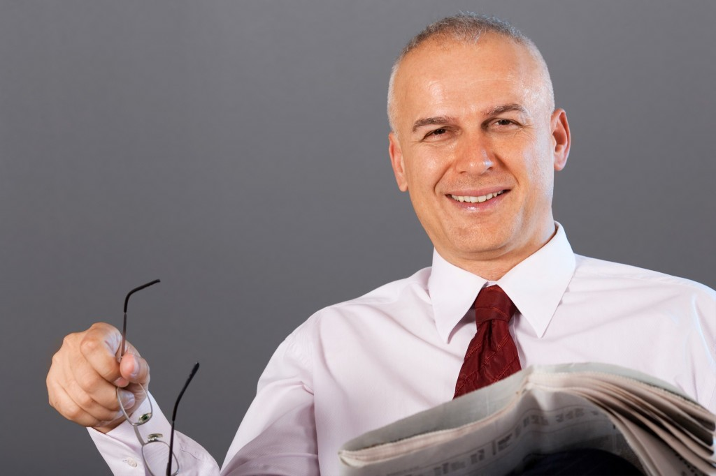 Middle aged businessman reading newspapers