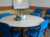 Mesa redonda para pequenos grupos. Quadro branco com suporte para flip-charts.